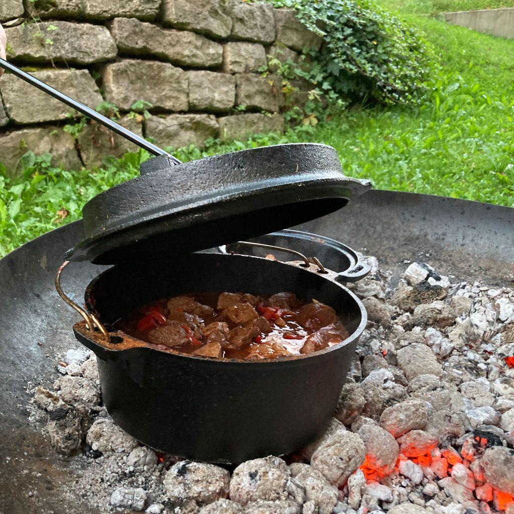 Gulasch im Dutch Oven über der Glut in der Feuerschale