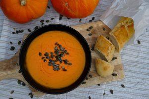 Kürbissuppe aus dem Dutch Oven serviert mit Kürbiskernen und Baguette