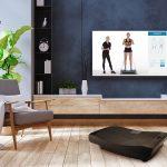 Wohnzimmerscenic mit 4D Vibrationsplatte V3000 und Trainingsvideo auf dem Fernseher