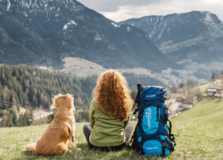 Bergpanorama mit Frau, Hund und Skandika Rucksack