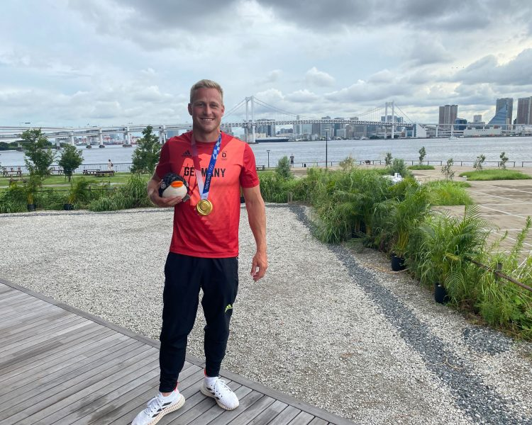 Max Rendschmidt mit Gold-Medaille vor der Regatta-Strecke in Tokio