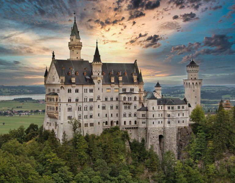 Schloss Neuschwanstein mit Bäumen und gelblichem Himmel