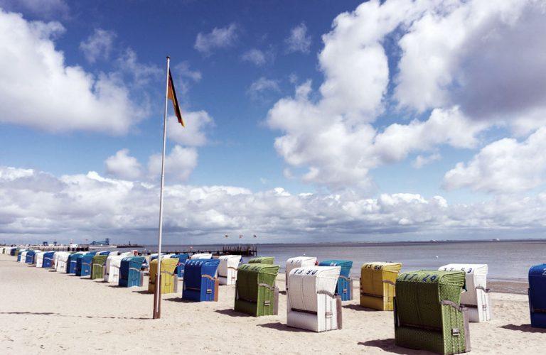 Sandstrand bei Ebbe mit bunten Strandkörben auf Föhr