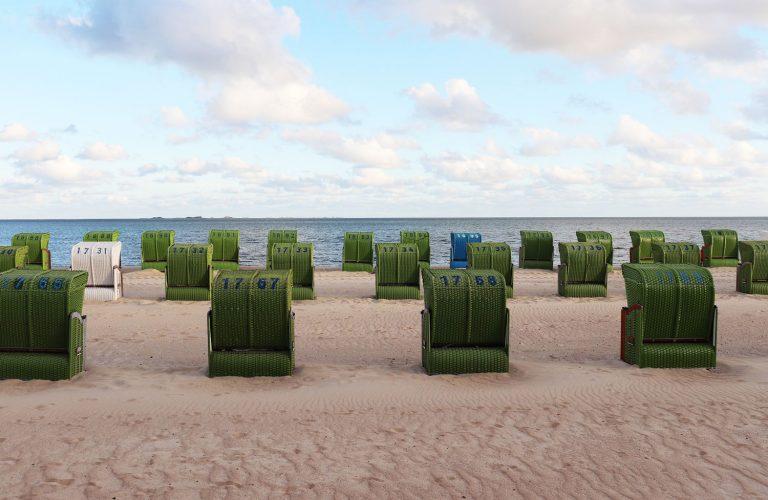 Grüne Strandkörbe am Föhrer Strand mit Meer