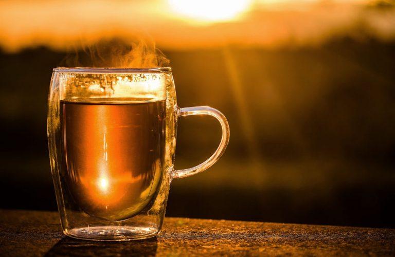 Warmer Tee in Glastasse vor Sonnenuntergang